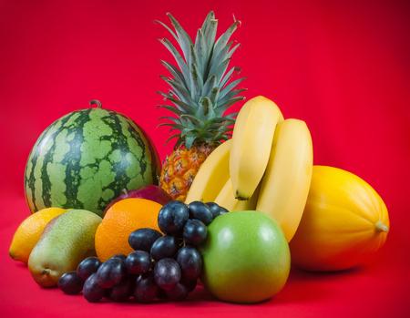 Fresh ripe exotic fruits on red background Stock Photo