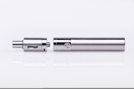 Disassembled e-cigarette atomizer and battery mod on white background