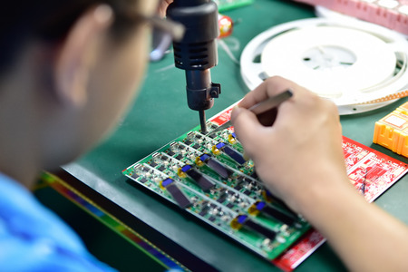 Engineer making a soldering on hardware microchip