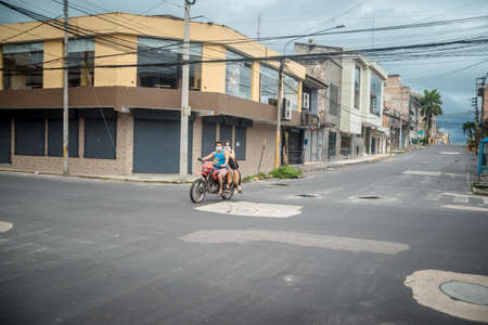 A people riding a scooter on a city street Editorial