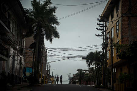 A street scene with two persons stnading on the road Editorial
