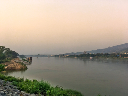rive: Mekong river and bridge crossing to Laos on evening with sunset and yellow sky. Big river at countryside with mountain and bridge on evening.