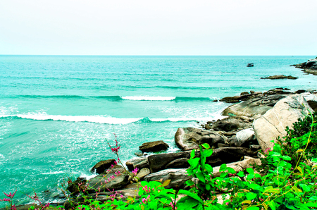 The view of sand beach and sea wave with rock and cloudy on afternoon, Beautiful of sand beach and sea and rock with fishing boat in the sea.