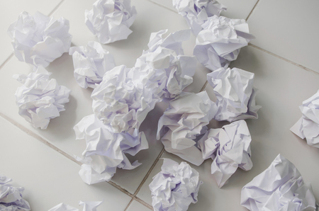 No idea and fail concept - Many crumpled paper or trash and white paper ball and waste on the floor. A hand are crumpling a paper, Recycling or fail creativity concept.