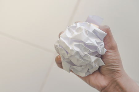 No idea and fail concept - Human hand holding crumpled paper or trash and white paper ball and waste on the floor, A hand are crumpling a paper, Recycling or fail creativity concept. Stock Photo
