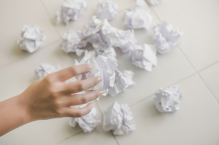 No idea and fail concept - Human hand holding crumpled paper or trash and white paper ball and waste on the floor, A hand are crumpling a paper, Recycling or fail creativity concept. Stock fotó