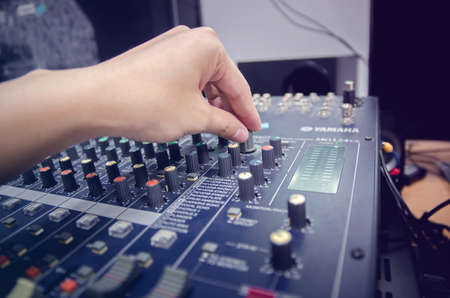 Audio mixer console and professional sound mixing. A hand is adjusting audio mixer with buttons and sliders. Mixer console for musician DJ and sound engineers.