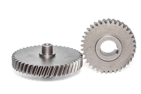 Two metal cog gears together on white background photo