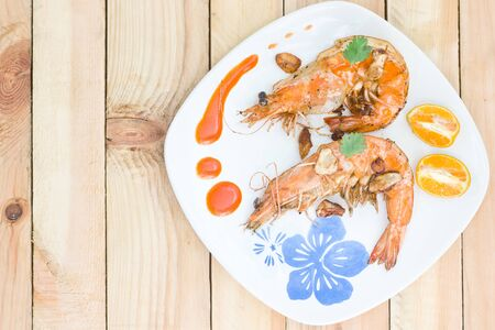 Fried shrimps on the white plate and vegetables.
