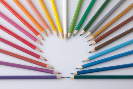 group of colorful color pencils heart shape on white background photo