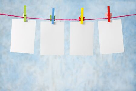 photo paper hanging on the clothesline on light blue background Stock Photo - 14511430
