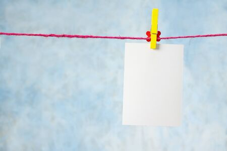 photo paper hanging on the clothesline on light blue background photo