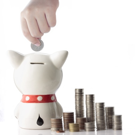 a hand saving coin in piggy bank on white background photo