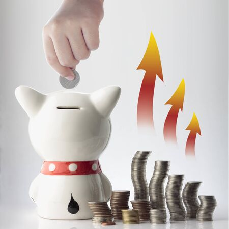 a hand saving coin in piggy bank with graphic on white background photo