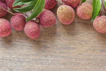 Lychee with leaves on a wooden table with space. Stock Photo