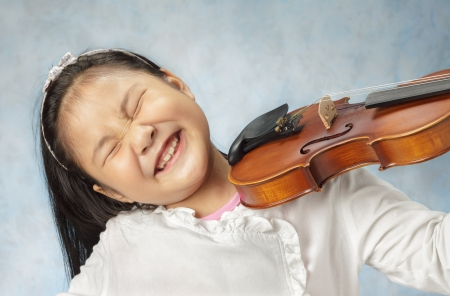 Cute little Asian girl playing the violin very enjoying . photo