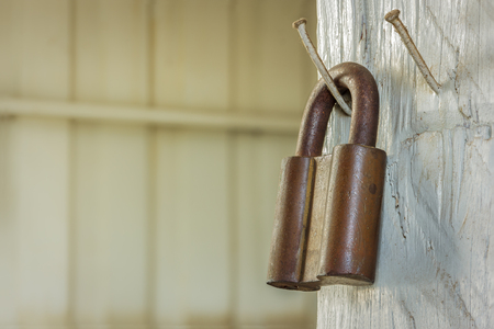 rusty old metal padlock hanging on wooden wall. photo