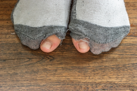 worn out socks with a hole and toes sticking out  of them on  old wooden floor   photo