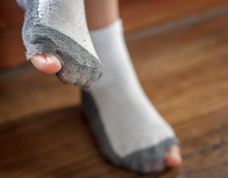 worn out socks with a hole and toes sticking out  of them on  old wooden floor