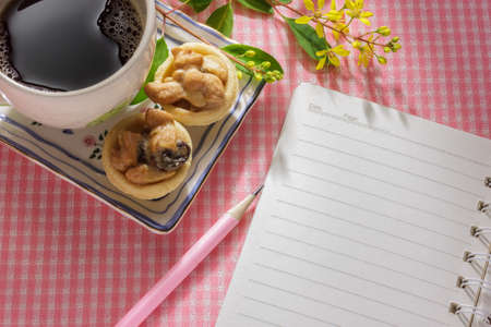 blank notebook on pink cloth table with a cup of coffee and dessert. photo