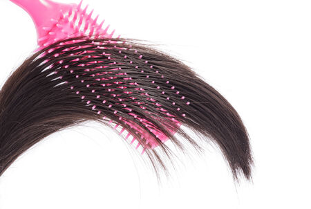 Black hair with pink hair brush on white background.