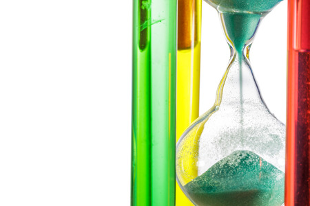 Colorful hourglass with green sand on white background. photo