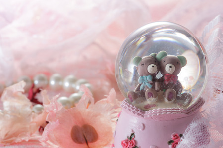 Teddy bear in snow globe decoration on pink fabric background,as valentines background. photo