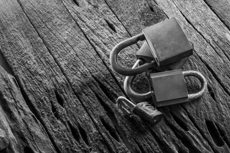 Old group of padlocks display on grunge wooden background,black & white. Stock Photo