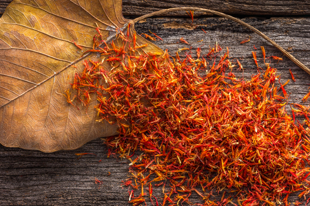 Dry Safflower with leaf  on grunge wooden background. Stock Photo