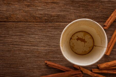 Empty coffee cup with Cinnamon after drink on wood table.