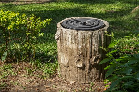 Trash bin In The Park With Tree Trunk Design. Stock Photo