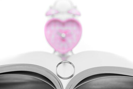 Close up wedding ring with  pink heart-shaped clock with white background. Stock Photo