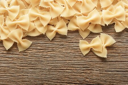 Dry butterfly pasta  on a wooden background. bow tie pasta.farfale Italian pasta.