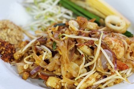 Classic Thai dish. Stir-fried noodles with shrimps, chicken, egg, bean sprouts, Lemon, scallions & crushed peanut. photo