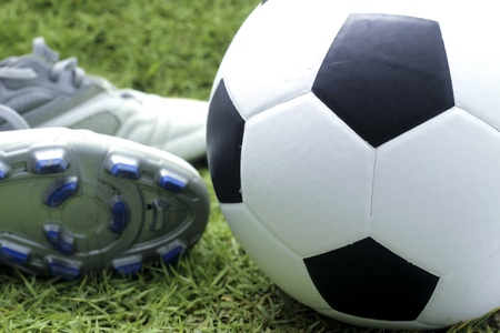 soccer shoes: Soccer ball and soccer shoes on the field of green grass