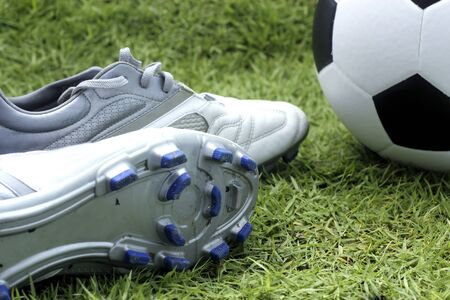 soccer shoes: Soccer shoes and soccer balls on the field of green grass
