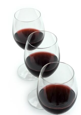 Three glasses of red wine on a white background. photo