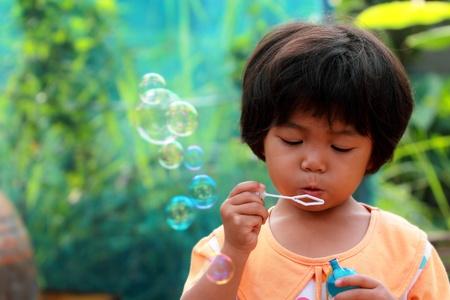 ni�os pobres: Chica tailandesa poco de soplar burbujas Foto de archivo