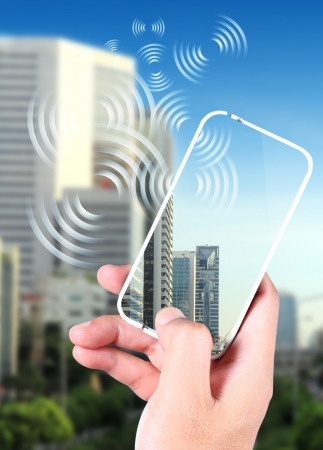 Hand holding smartphone with a contemporary, have a clear picture on the screen, the image of the citys skyscrapers blur the background photo