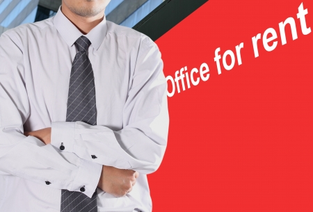 Cropped view of Businessman standing in front of a billboard with a red office for Rent photo