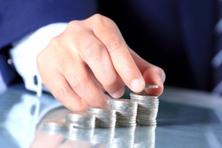 Businessman hand put coins, Making money concepts photo