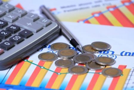 Coin, calculator, pen on graph photo