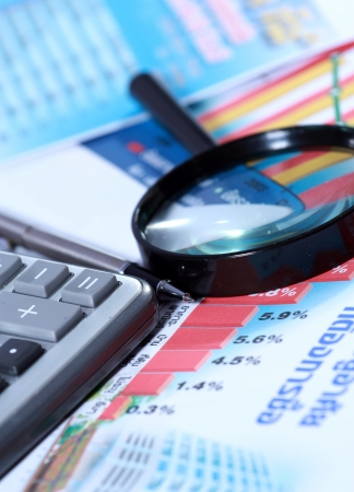 magnifying glass, calculator and pen on graph Stock Photo - 14873242