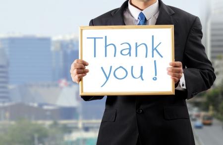 Businessman holding Whiteboard mit einer Nachricht danke. Standard-Bild