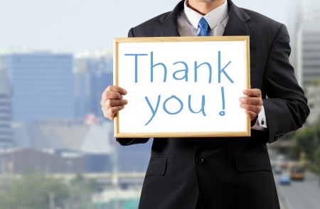 appreciate: Businessman holding whiteboard with a message thank you.