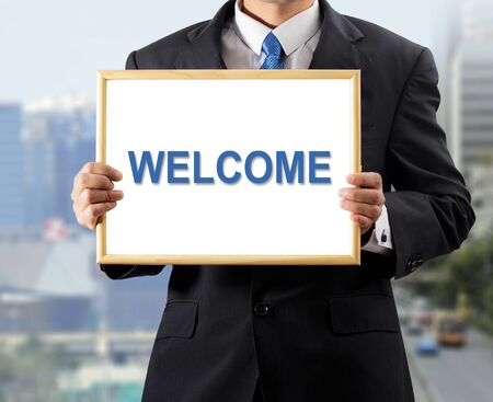 Businessman holding whiteboard with a message WELCOME photo