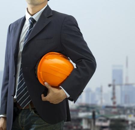 ingenieria industrial: Recortada vista de la legitimaci�n casco ingeniero que sostiene en frente de la ciudad Foto de archivo