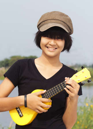 Little girl play guitar, look to the camera and smile in outdoor photo