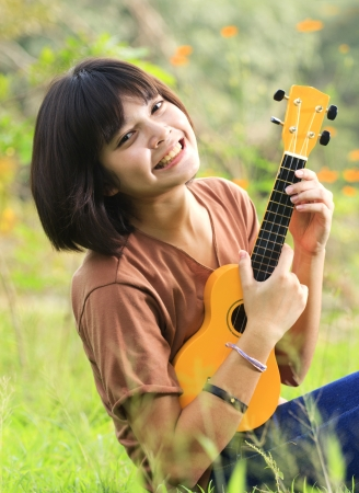 Young girl play guitar, look to the camera and smile in outdoor photo
