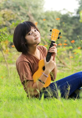 Young girl playing guitar, look to the camera and smile in outdoor photo